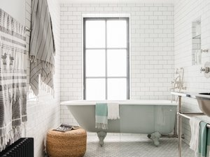 white modern bathroom with freestanding clawfoot tub and a window behind it