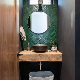 A bathroom sink with a pine green backsplash and round mirror