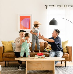 Two women playing with their kids in their living room