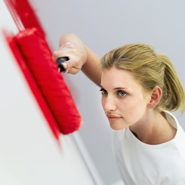 high angle view of a young woman painting a wall red with a paint roller