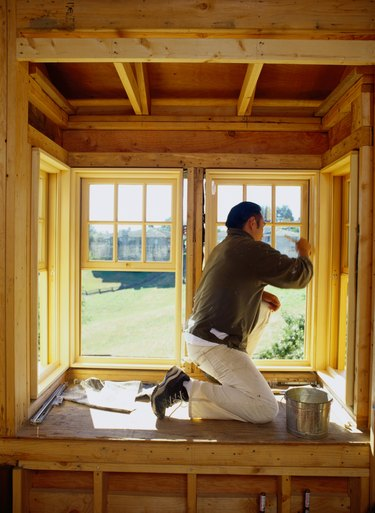 Man painting bay window frame