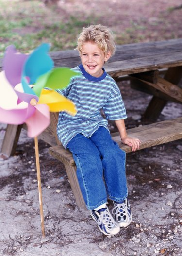 portrait of a boy sitting on a picnic table (6-8) with a toy windmill