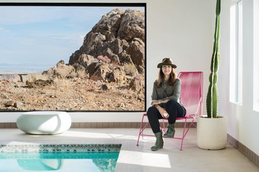 Kelly Van Patter sits by the inside pool on a pink mid-century style lounge chair by a large slider window with desert view.