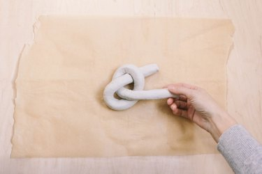 Pulling tail of air dry clay through hole to form a knot