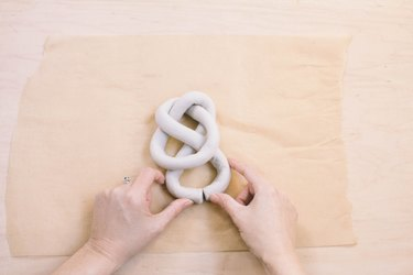 Closing tails of air dry clay sculpture to form a knot
