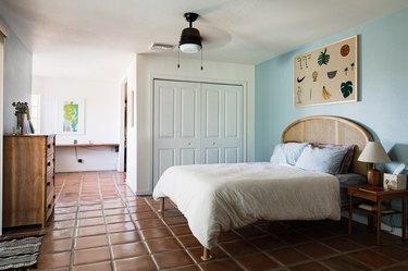 Saltillo tile floor in bedroom with ceiling fan