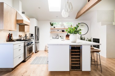 open kitchen with large island, wood floor, overhead wood beam, white lower cabinetry and wood uppers