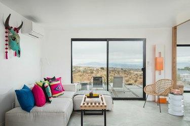 A slider door reveals view of desert from living room area.