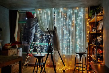 bedroom with fairy light curtains over windows