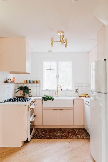 kitchen with pink cabinets and white walls