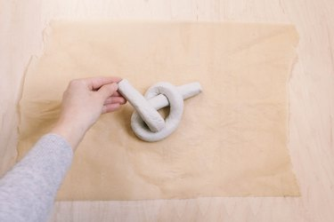 Folding tail of air dry clay up to form a knot