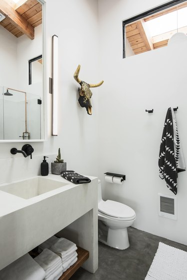 A white concrete bathroom with sink and toilet.