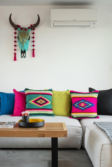 Color textiles pillows, a painted cattle skull and sectional couch.