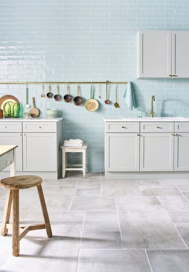 kitchen space with blue walls and white cabinets with light porcelain flooring