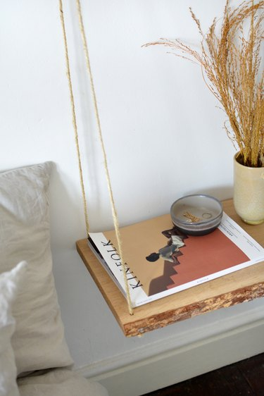 Wooden shelf suspended from rope with a magazine and grey bowl and beige vase.