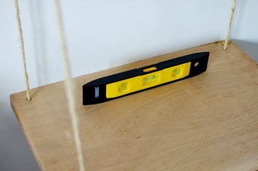 A piece of wood hangng from natural rope with a black and yellow spirit level on top