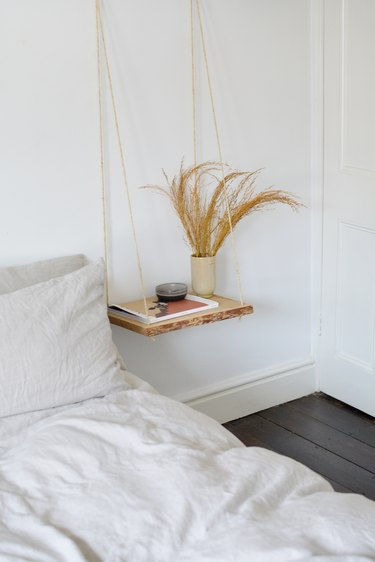 Floating wood nightsand with dried grasses next to a beige bed