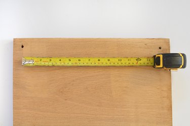 Piece of wood with a tape measure extended to mesure the length