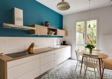 Scandinavian kitchen floor tile with pattern and white cabinets with wood countertop