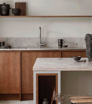 dark wood cabinets with steel countertop and limestone counter at island
