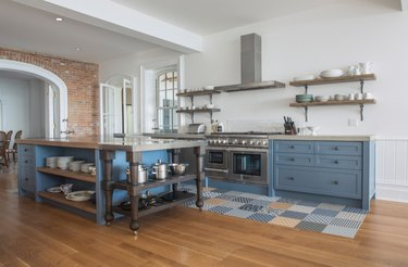 Scandinavian kitchen floor tile in patchwork pattern with blue cabinets