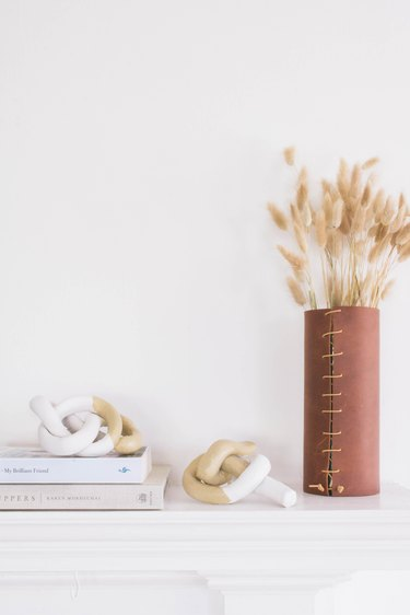 two clay knot sculptures on a mantel with books and dried flowers