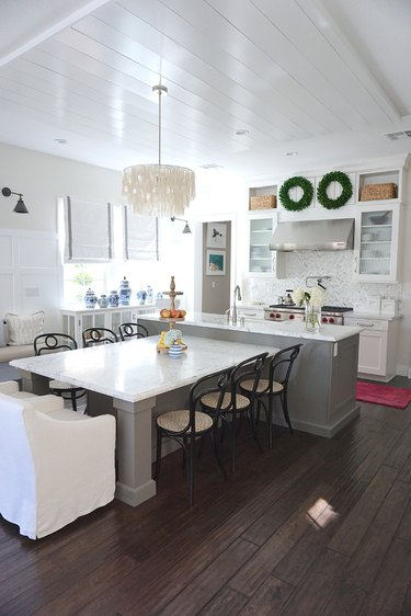 T-shaped kitchen island with a variety of chairs and chandelier in farmhouse kitchen