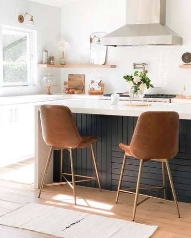 midcentury kitchen island idea with contrasting black back panel and white countertops