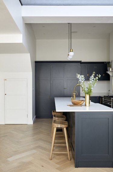 Herringbone kitchen floor with navy blue cabinets and simple decor
