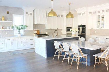 Navy blue and marble T-shaped kitchen island with gold pendant lights