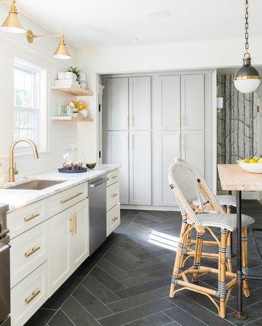 Gray tile herringbone kitchen floor in white, airy kitchen and brass details