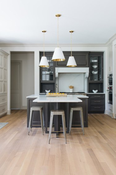 Navy blue T-shaped kitchen island with three gold and white pendant lights