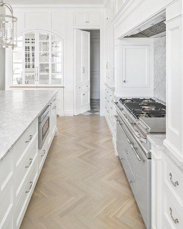 Light wood herringbone kitchen floor in white, minimalist kitchen