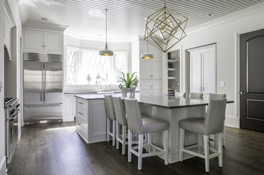 White T-shaped kitchen island with upholstered chairs, pendant lights, and geometric chandelier