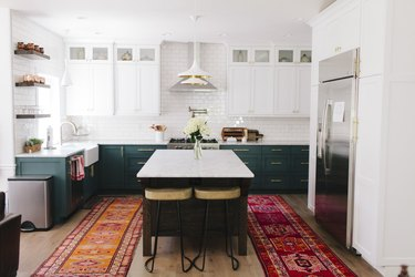 espresso kitchen island with green cabinets and colorful runners