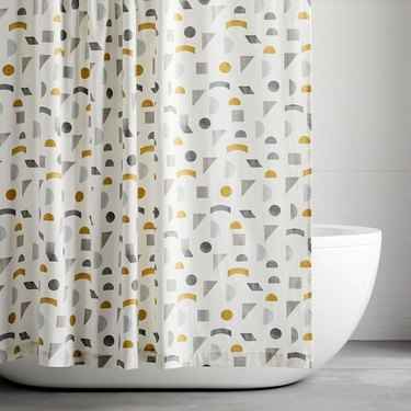 Yellow, white, and gray midcentury modern eco-friendly shower curtain in white bathroom