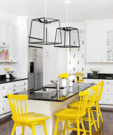 beadboard kitchen island with black granite countertop and yellow counter stools