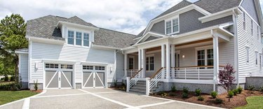white and gray house exterior with carriage style garage doors
