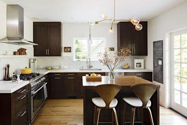 espresso kitchen island in midcentury space with dark cabinets