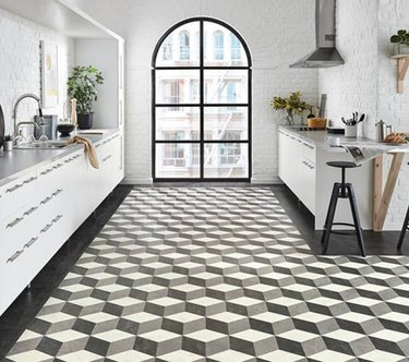 Three dimensional stepped pattern tile floor in a white modern kitchen with large picture window.