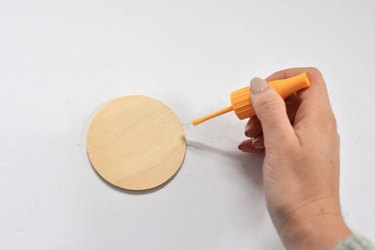 Hand holding brush with glue against wooden circle.
