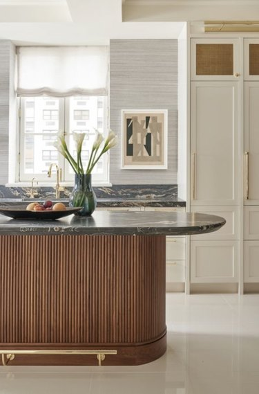 Oval kitchen island with dark gray marble countertop, wood base and brass hardware.