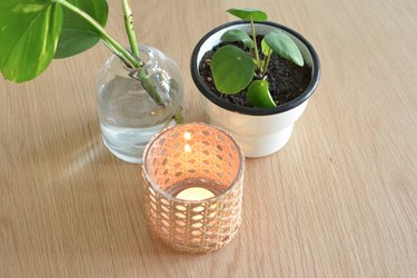 Cane candle holder with lit tealight candle inside. Next to plant pot and a glass vase with plant inside.