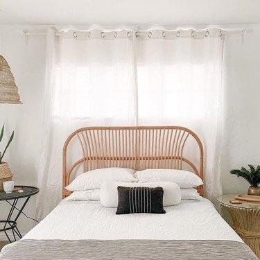 rattan Scandinavian headboard in neutral bedroom with woven pendant