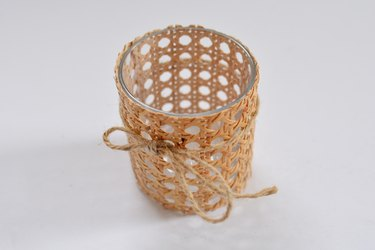 cane wrapped around glass with jute string tied around.