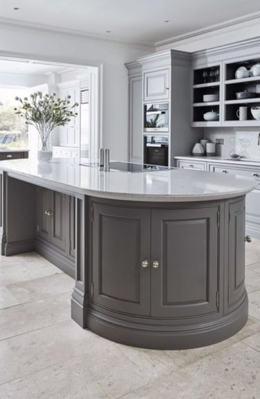 Oval shaped kitchen island with gray cabinets and white countertop.