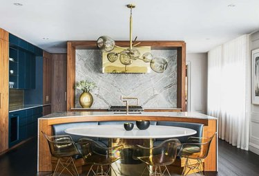 Cut out kitchen island with marble countertop, built-in oval dining booth, white dining table with brass finish base.