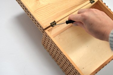 Hand holding screwdriver while screwing lid back onto box.