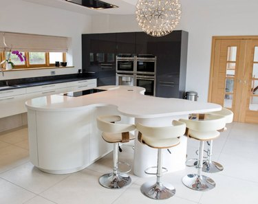Oval kitchen island with curved dining area connected. All white cabinets and countertop.