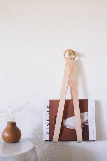 diy leather & wood magazine holder hanging on wall with kinfolk magazine inside